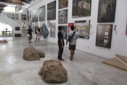 Rocks and stones and people in the middle of the gallery.